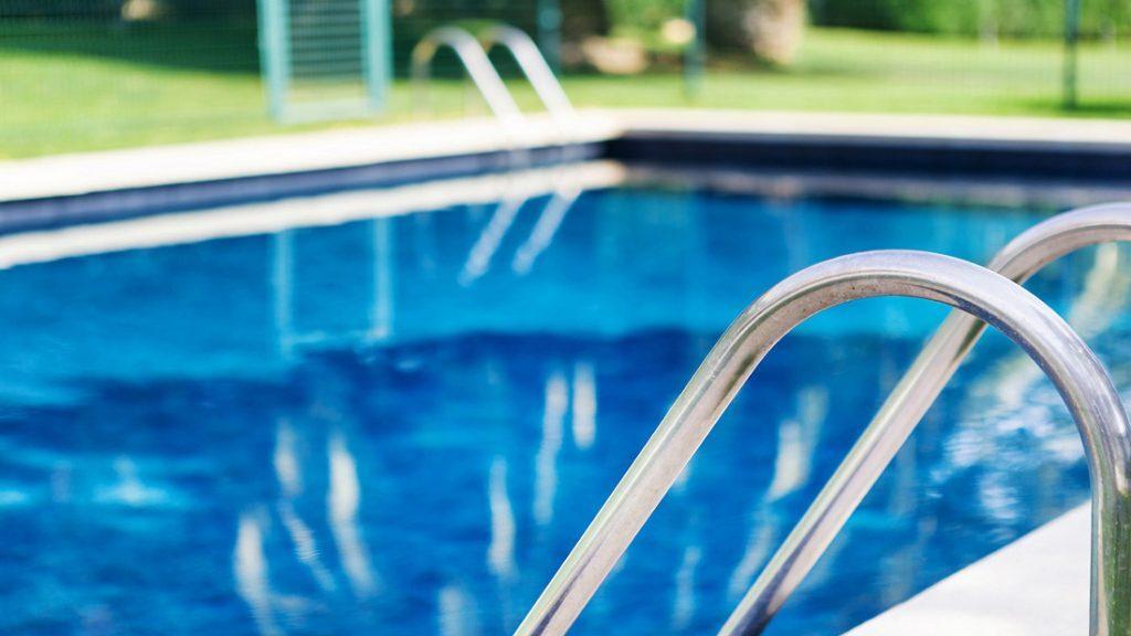 """Sfeerbeeld van een rechthoekig buitenzwembad met 2 trappen, afgewerkt met folie Alkorplan Touch textuur """"Elegance"""""""