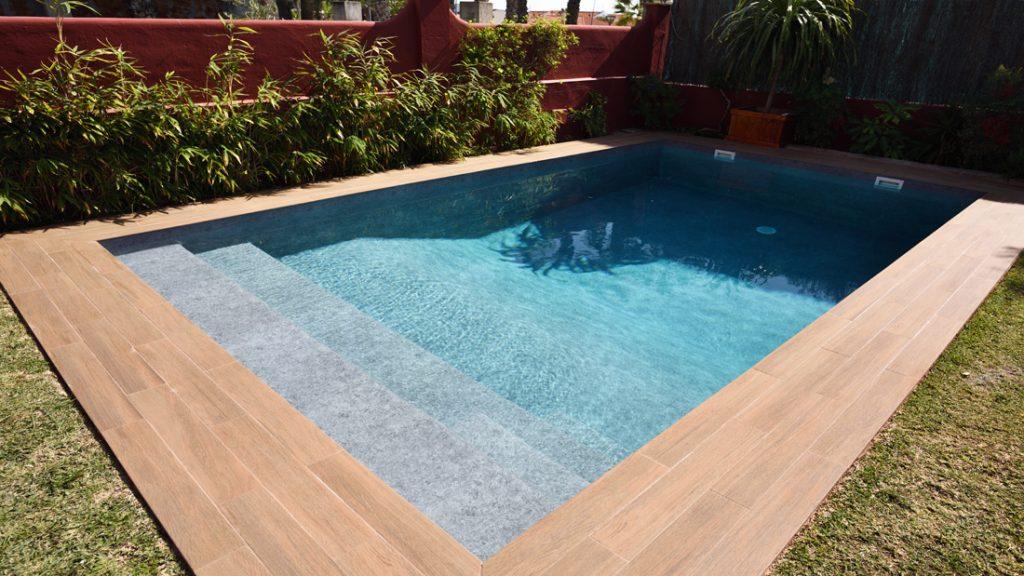 """Sfeerbeeld van een buitenzwembad met houten boord,en brede ingewerkte trap afgewerkt met folie Alkorplan Touch textuur """"Prestige"""""""