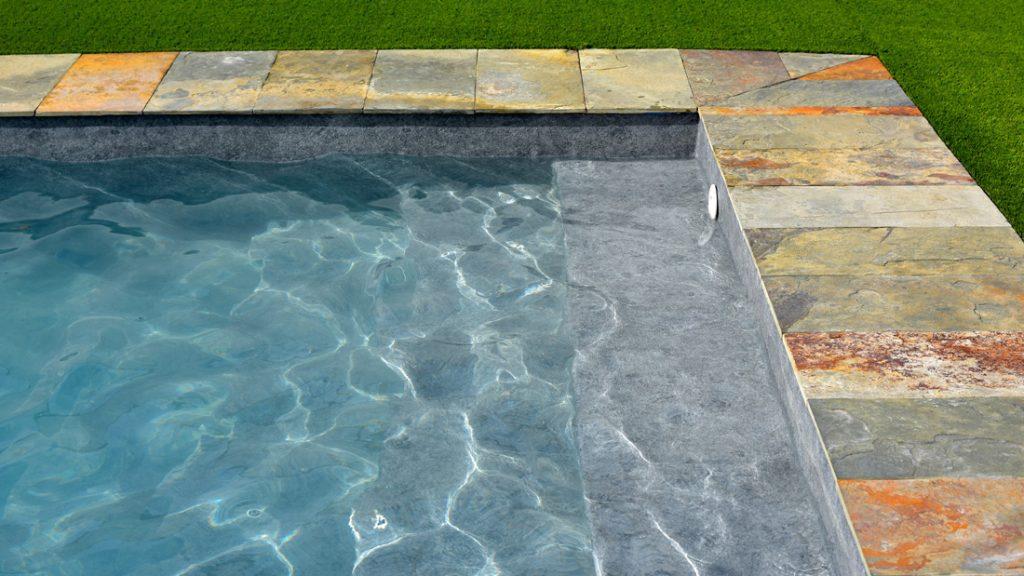 """Sfeerbeeld van een buitenzwembad met stenen boord, afgewerkt met folie Alkorplan Touch textuur """"Prestige"""""""