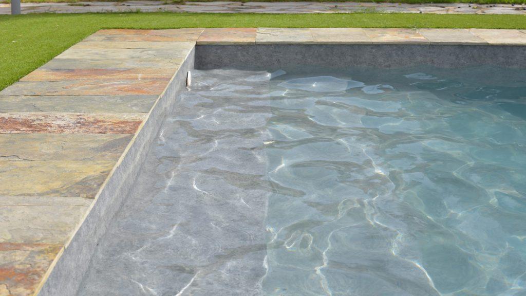 """Sfeerbeeld van een buitenzwembad met stenen boord en brede ingewerkte trap, afgewerkt met folie Alkorplan Touch textuur """"Prestige"""""""