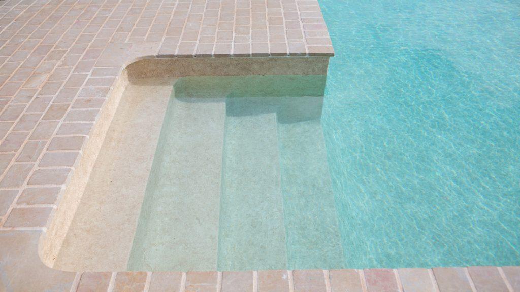 """Sfeerbeeld van een buitenzwembad met ingebouwde trap, afgewerkt met folie Alkorplan Touch textuur """"Sublime"""""""