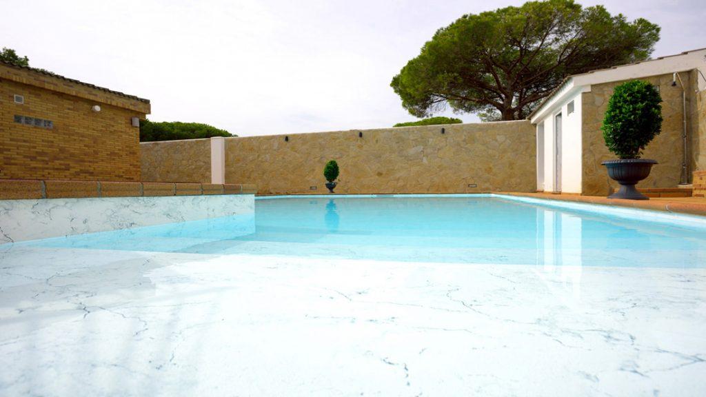 """Sfeerbeeld van een buitenzwembad met ingebouwde trap, afgewerkt met folie Alkorplan Touch textuur """"Vanity"""""""