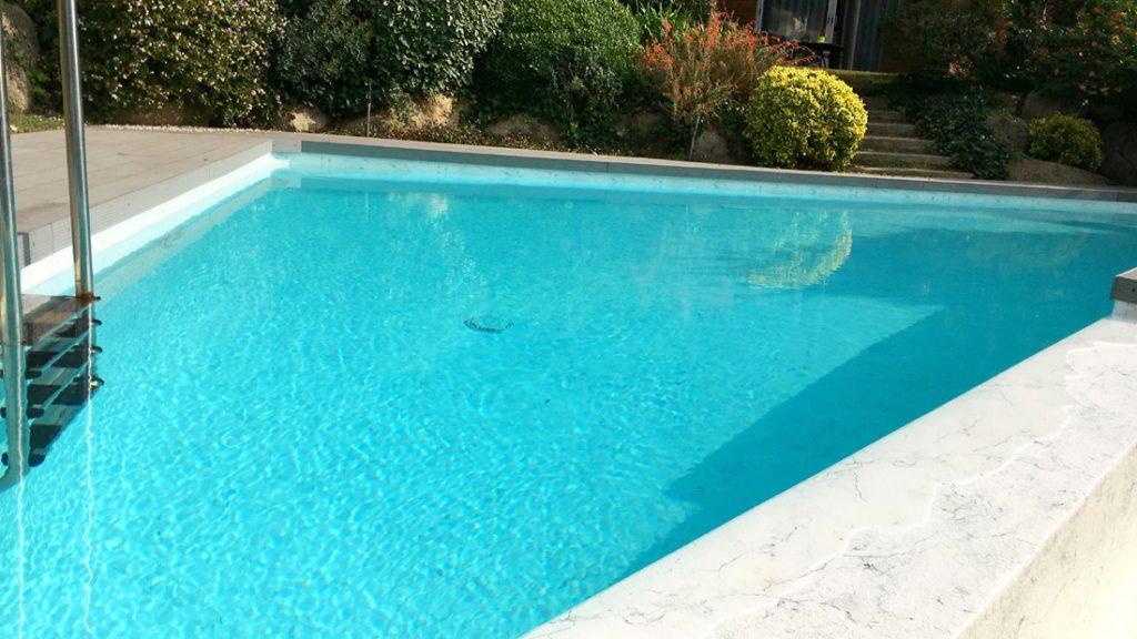 """Sfeerbeeld van een trapeziumvormig buitenzwembad, afgewerkt met folie Alkorplan Touch textuur """"Vanity"""""""